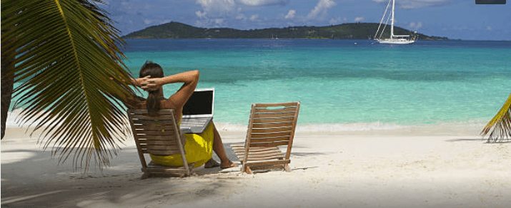 Business woman working on a laptop on a Caribbean beach