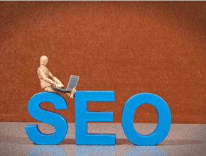 Cartoon figure sitting with a laptop on top of the letters SEO (Search Engine Optimization)
