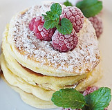 Stack of pancakes sprinkled with powdered sugar, garnished with raspberries and mint leaves