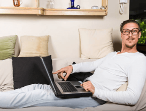 Handsome Man sitting comfortably on sofa working on laptop
