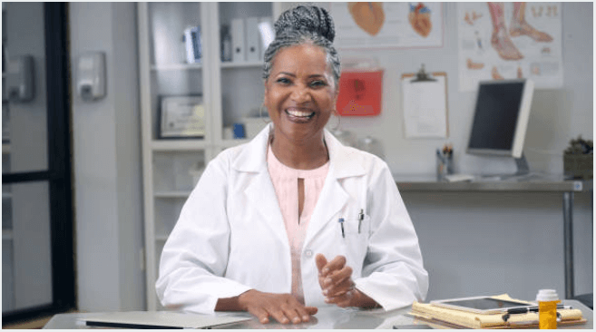 Cheerful Retired Lady science teacher wearing a lab coat sitting at a desk with her PC tablet