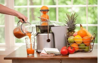 Juicer Machine, fruit basket and fresh juice on a worktop