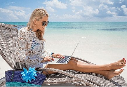 Pretty lady sitting on beach chair working on laptop