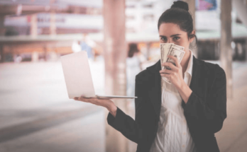 Happy woman holding laptop in one hand and money on the other hand