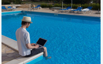 Man working on laptop with his feet dipped in the swimming pool