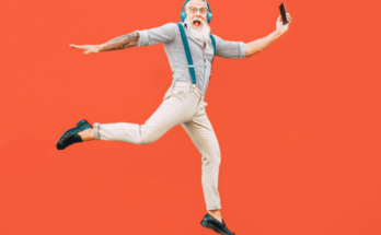 Funky Looking Energetic Elderly man Jumping High Cheerfully With Cell Phone in Left Handly